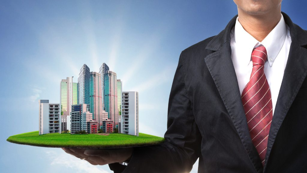 A Business man holding the real estate bulding kit.